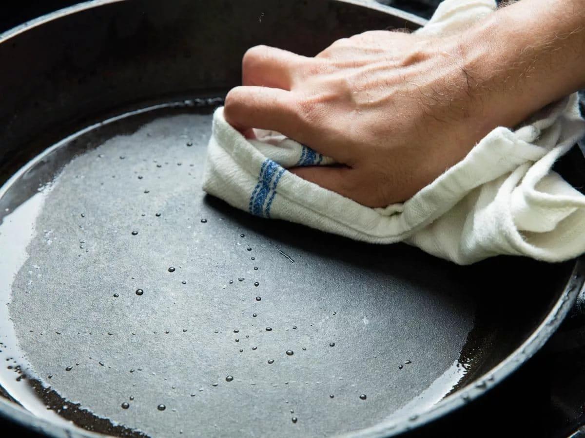 Прожарювання чавунної сковороди перед першим використанням в домашніх умовах: підготовка, як прожарити з сіллю і маслом, як загартувати на плиті